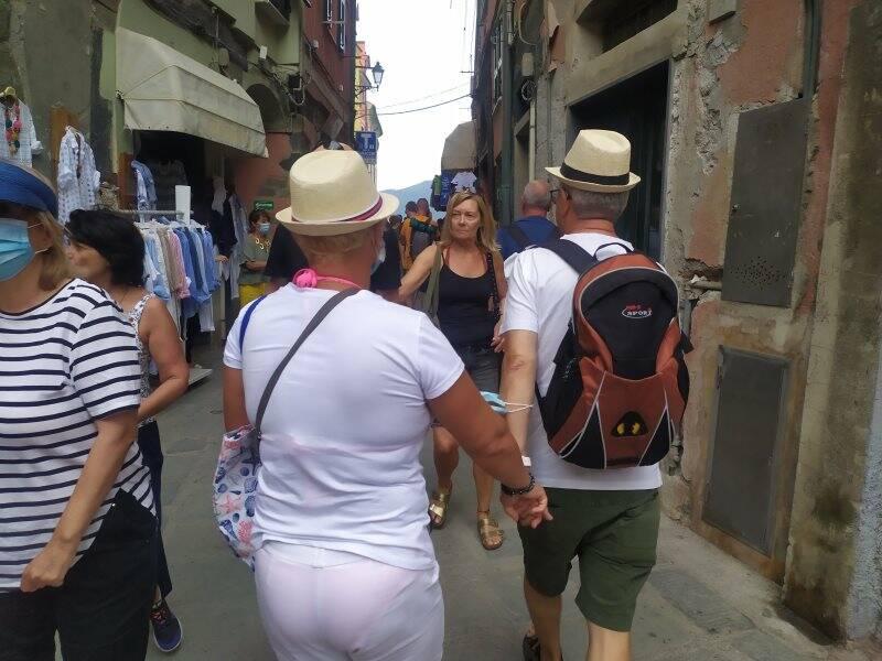 Una coppia di turisti si tiene per mano tra le vie di Vernazza